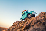 travel and adventure concept: toy retro car on rock