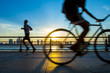 Silhouettes of jogger running and bicyclist cycling at sunset in front of the city skyline