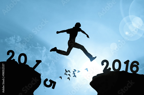 Poster Man jumping over precipice on sunlight background , new year con