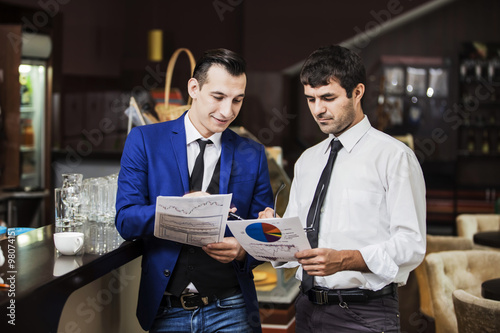 Poster Два друга весело обсуждают в кафе общий бизнес