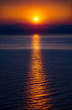The Rising Sun Over the Sea with Beautiful Vibrant Red Glow and Reflection on the Water. Mountains in Background.