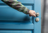 man holding on to by its metal handle in the open wooden door blue - 98125776