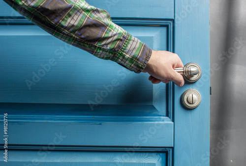 Poster man holding on to by its metal handle in the open wooden door blue