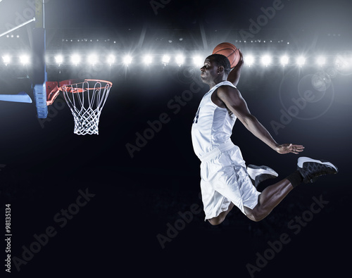 Fotografiet Basketball Player scoring a slam dunk basket