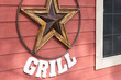Rusty metal star sign hanging on a wooden wall of a grill place