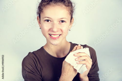 obraz lub plakat Child Hygiene.Little girl cleaning her hands with a wet baby wipe isolated on a white background.
