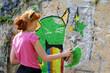 Jungendliche sprüht Graffiti an Fassade
