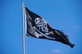 Skull and crossbones Jolly Rogers black flag flying on a flag pole
