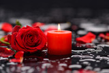 Red rose, petals with candle and therapy stones