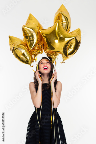 Poster Joyful beautiful young female looking up on star shaped balloons
