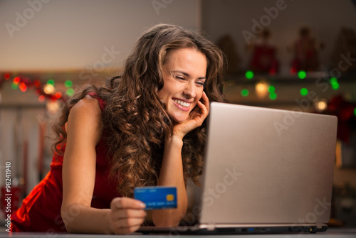 Poster Woman with credit card choosing Christmas gifts on laptop