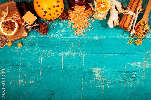 spa concept on wooden background: Aromatic oils, salt, soap, citrus, cinnamon candles. top view