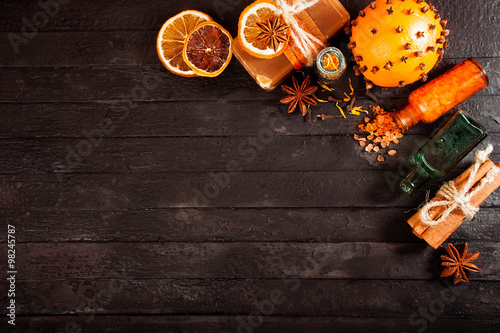 spa concept on wooden background: Aromatic oils, salt, soap, citrus, cinnamon candles. top view
