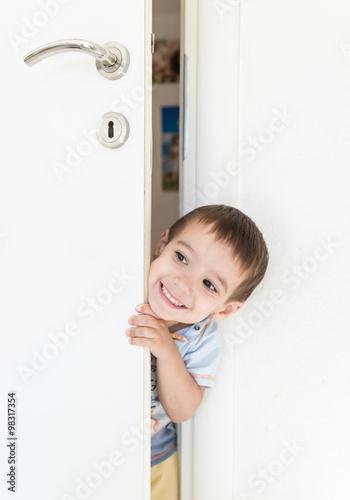 Poster Kid peeking out of the open room door