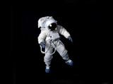 Astronaut floating against a black background. - 98356764