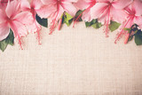 Pink Hibiscus flowers on linen, copy space background, selective - 98359375