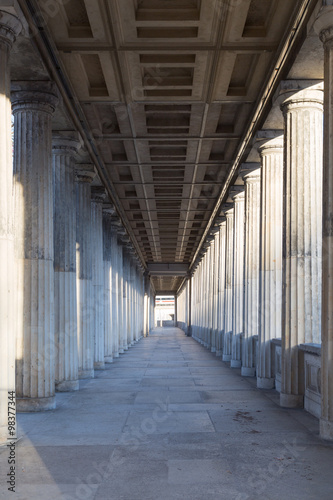 Fototapeta A long corridor between many columns in a historical building in berlin