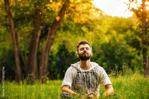 A man sitting on grass in the park and smiling with eyes closed