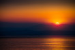 The Rising Sun Over the Sea with Beautiful Vibrant Red Glow. Mountains in Background.
