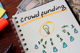 Notebook with crowd funding  sign on a table. Start up concept.