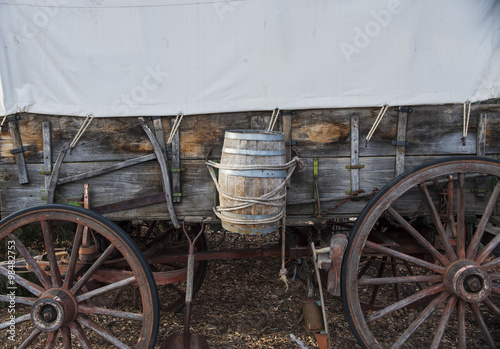 Side view of pioneer wagon with water barrel and canvas top Poster