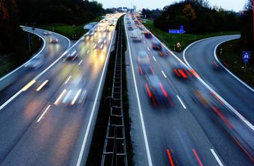 Autobahn bei Augsburg in Bayern bei Nacht mit Lichtspuren der Autos