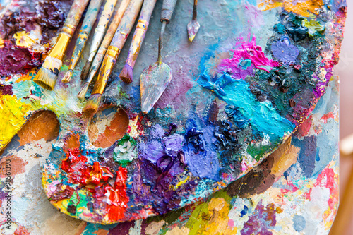 Fototapeta Closeup of art palette with colorful mixed paints and paintbrushed