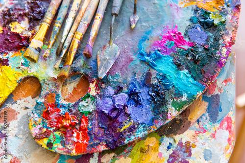 Fototapeta samoprzylepna Closeup of art palette with colorful mixed paints and paintbrushed
