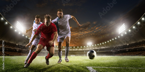 Fototapeta Soccer players in action on sunset stadium background panorama