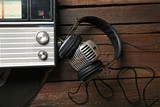 Fototapeta Radio with headphones and microphone on wooden background