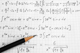 Maths concept - handheld calculator and pencil over a sheet of paper with maths-formulas - 98638570