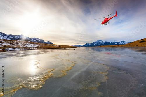 Poster Elicottero rosso in volo su lago ghiacciato