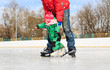 father and little daughter learning to skate in winter