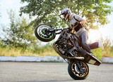 Fototapety His true passion. Full length soft smudged focus portrait of a man practicing stunts on a motorbike outdoors