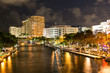 Night view of New River with Riverwalk promenade highrise condominium buildings and yachts in Fort Lauderdale, Florida, USA