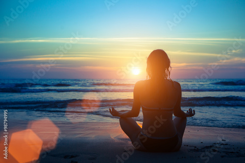Poster Silhouette young woman practicing yoga on the beach at sunset.