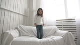 little Asian girl jumping on bed, slow motion