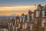 Typical British brick houses on a cloudy morning with sunrise and Canary Wharf at the background. Panoramic shot from Muswell Hill, London, UK