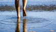 Young Woman's Feet Walking in the Sand and water