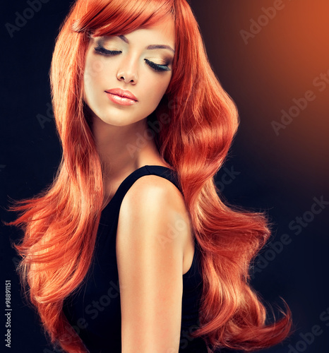 Fototapeta Beautiful model girl with long red curly hair . Hairstyle and cosmetics