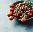 Cherry tomatoes on the vine in a ceramic bowl