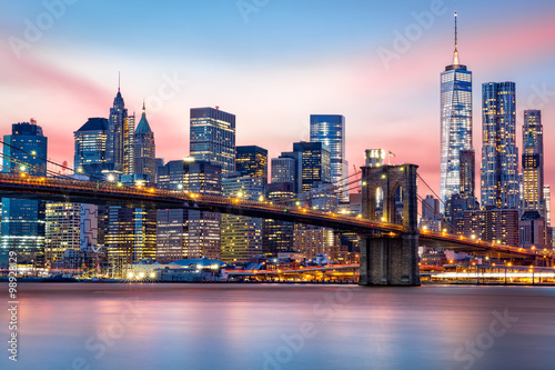 Brooklyn Bridge at and the Lower Manhattan skyline under a purple sunset Poster