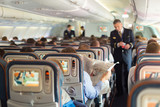 Fototapety Steward and passengers on commercial airplane.