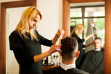 Female hairdresser cutting hair of smiling man client at beauty