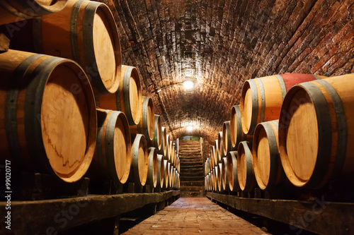 Poster, Tablou Oak barrels in a underground wine cellar