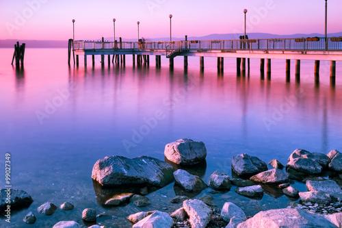 Surreal pink sunset long exposure, Bracciano Lake at Anguillara Sabazia, Lazio, Italy.