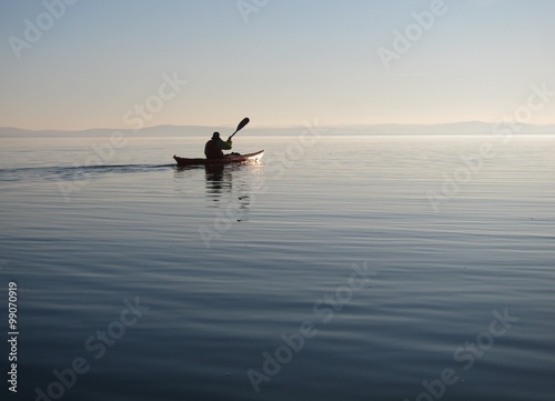 Man on wooden self-made kayak in calm blue lake