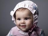 Bebé con gorrito y lazo rojo con gesto de curiosidad