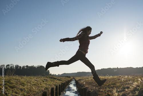 Poster 小川を飛び越える女性