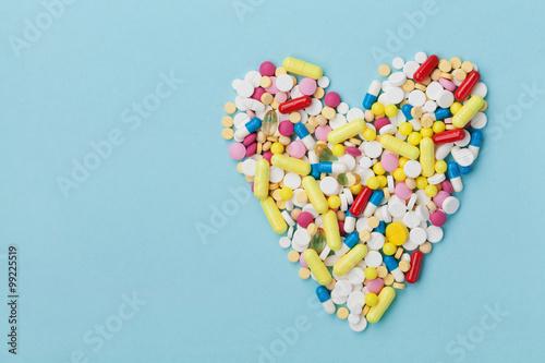 Colorful drug pills in shape of heart on blue background, pharmaceutical concept Plakat